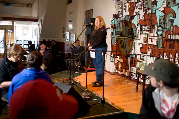 """Kate Morgeneir recites Emily Dickinson's """"Hope"""" at a gathering of the Mad Poets Society in Phoenixville. Mad Poet Missy Grotz,a Media resident, calls the group """"the most wonderful bunch of insane people you could hope to be friends with."""""""