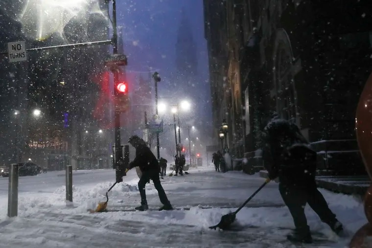 A group of people shovel the street by Broad and Cherry streets in Philadelphia while heavy snow falls on Wednesday, Dec. 16, 2020. The region is currently under a Winter Storm warning.