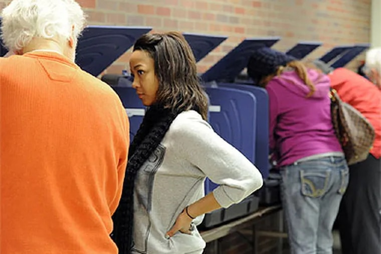 """""""I was just happy to get in,"""" said Chelin Lyles, second from left, a first-time voter from Evansville, who listens to election deputy, Don Assalone, left, as he tells her how to work the voting machine on the last day of early voting at the Civic Center in Evansville, Ind. on Monday, Nov. 5, 2012. (AP Photo/ The Evansville Courier & Press, Molly Bartels)"""
