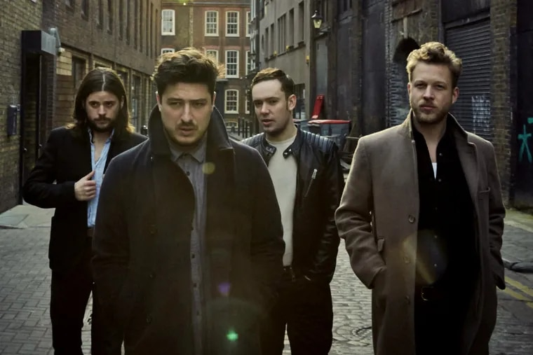 """Mumford & Sons members (from left) Winston Marshall, Marcus Mumford, Ben Lovett, and Ted Dwane. The Grammy-winning folk band has gone electric on """"Wilder Mind,"""" its third album. """"I don't think we ever felt like purists to one set of instruments or one style of songwriting,"""" says lead vocalist Mumford. (James Minchin III)"""