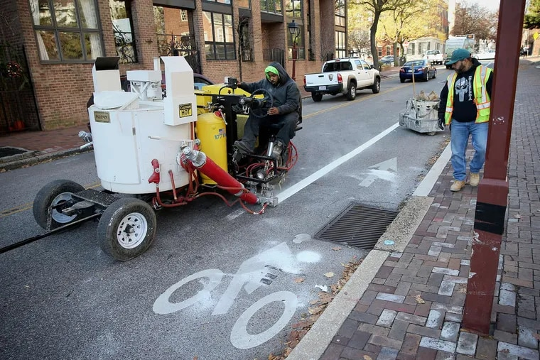 Darryl Carroll, Philadelphia Streets Department line striper crew chief, left, repaints a bicycle lane line on Spruce Street as fellow worker Jose Gonzalez follows his progress on Saturday, Dec. 2, 2017. The restriping, which was previously scheduled, took place days after a bicyclist was killed in a crash at Spruce and 11th streets.