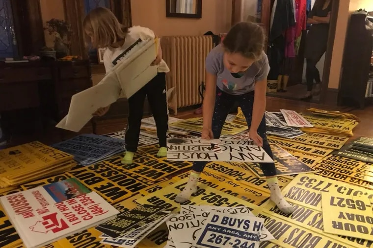 Froehlich's daughter, Zora Gilbertson, 8, (right) lays the signs out with friend Jaiel Lapp Yoder, 9 (left) in Froehlich's West Philadelphia home.
