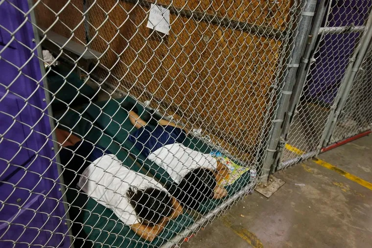 FILE – In this June 18, 2014 file photo, two female detainees sleep in a holding cell, as the children are separated by age group and gender, as hundreds of mostly Central American immigrant children are being processed and held at the U.S. Customs and Border Protection Nogales Placement Center in Nogales, Ariz.  The photos were taken by The Associated Press in 2014, when President Barack Obama was in office.