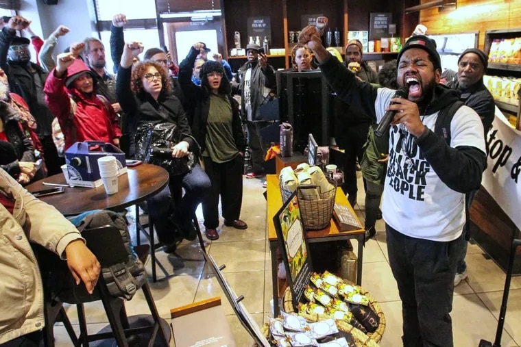 Protestor Anthony Smith, right, leads a chant, inside the Starbucks at 18th and Spruce Streets, in Philadelphia, April 16, 2018. Protesters are angry over the arrest last week by Philadelphia police of two African-American men inside this Rittenhouse Square area coffeeshop.