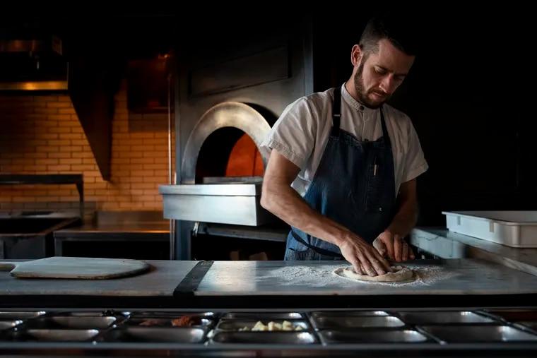 Jim Burke, the new chef at Wm. Mulherin's Sons, prepares a pizza at the restaurant in Philadelphia, Pennsylvania on Thursday, December 12, 2019.