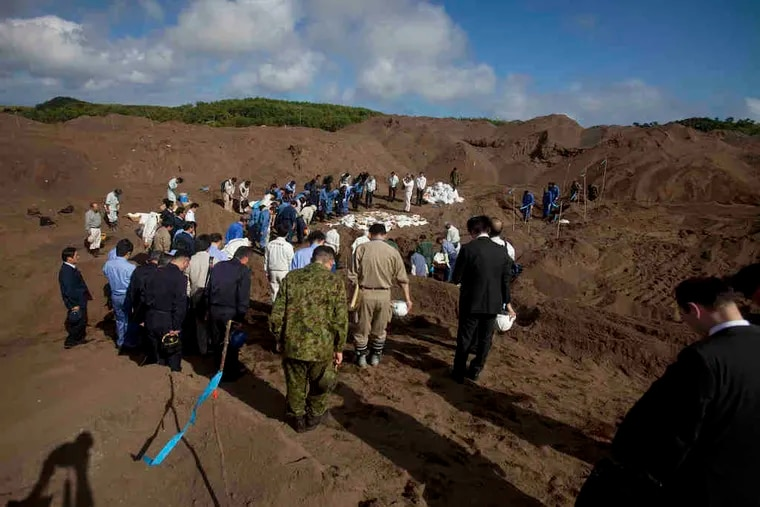 Japanese officials bow at a mass grave site on Iwo Jima, where the remains of Japanese soldiers from WWII have been discovered.