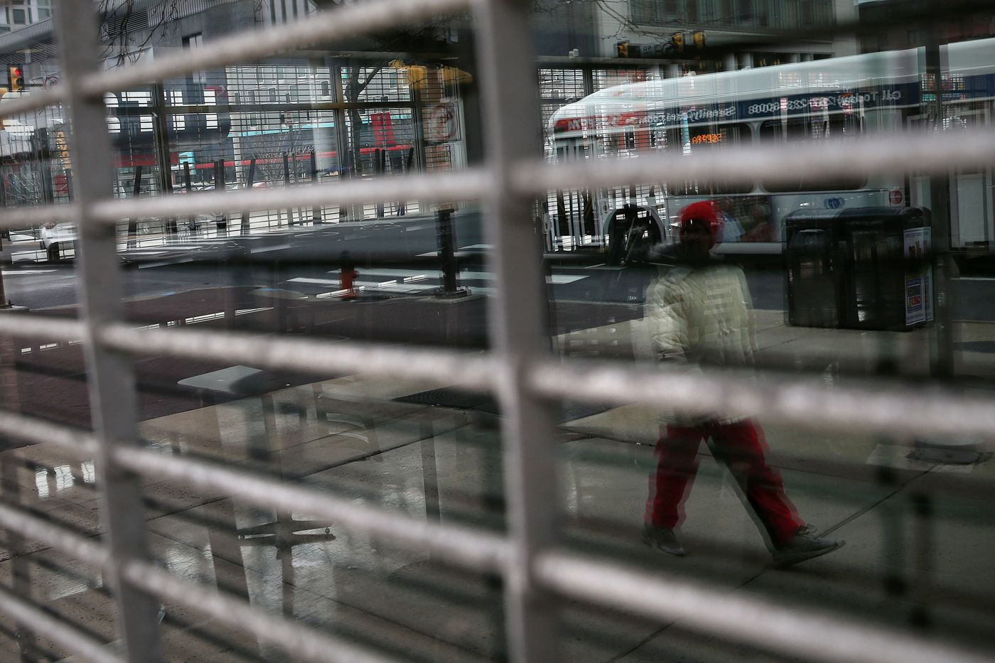 A pedestrian is reflected while walking past the shuttered Barnes and Noble on Temple University's campus in North Philadelphia on Tuesday, March 17, 2020. The university has transitioned its classes online due to the ongoing coronavirus pandemic, and nonessential retail businesses have been ordered to shut down.
