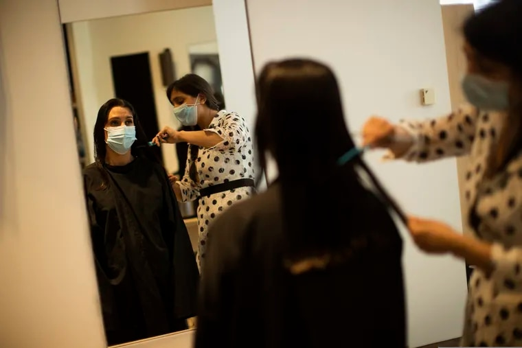 A client, wearing a mouth mask, gets her hair cut at the Maison L hair salon during the partial lifting of coronavirus, COVID-19, lockdown regulations in Brussels, Monday, May 18, 2020. Belgium is taking the next step in its relaxation of the coronavirus lockdown on Monday, with more students going to school, markets and museums reopening and the snip of a barber's scissors filling the air again. (AP Photo/Francisco Seco)