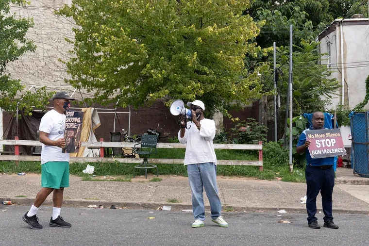 Anti-gun violence activists (left to right) Jamal Johnson, Leroy Muhammad, and Bhoke Lumumba on the 1800 block of West Susquehanna Avenue in Philadelphia on July 16, the day after a triple shooting in which a 14-year-old girl was shot by a stray bullet in front of her home.