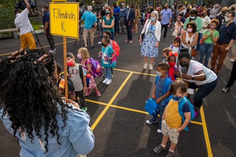 Jamila Hendricks, a kindergarten teacher, waits to escort her students into school on the first day of school on Aug. 31.