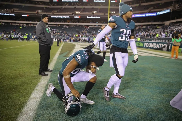 Eagles wide receiver Greg Ward, kneeling, is comforted by Eagles cornerback Craig James as they absorb the loss to the Seahawks.