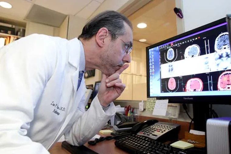Dr. Lee Adler of the Adler Institute for Advanced Imaging looks over the scans of a patient's brain.  ( Charles Fox / Staff Photographer )