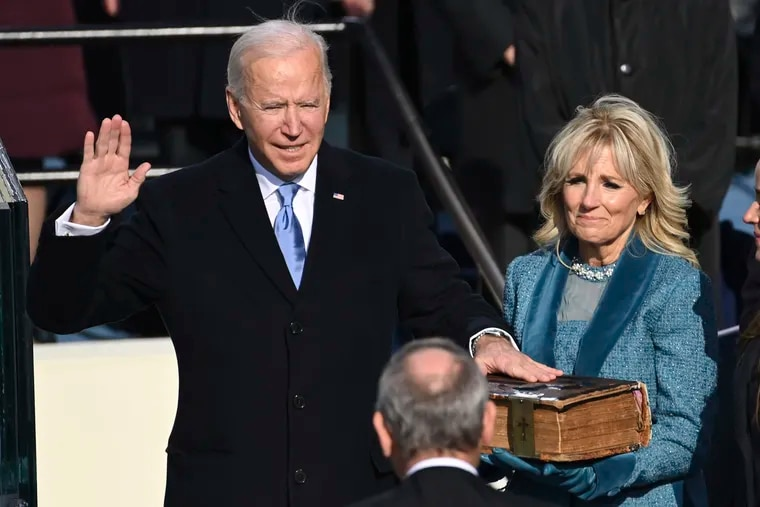 Joe Biden is sworn in as the 46th president of the United States by Chief Justice John Roberts as Jill Biden holds the Bible during the 59th presidential inauguration at the U.S. Capitol in Washington.