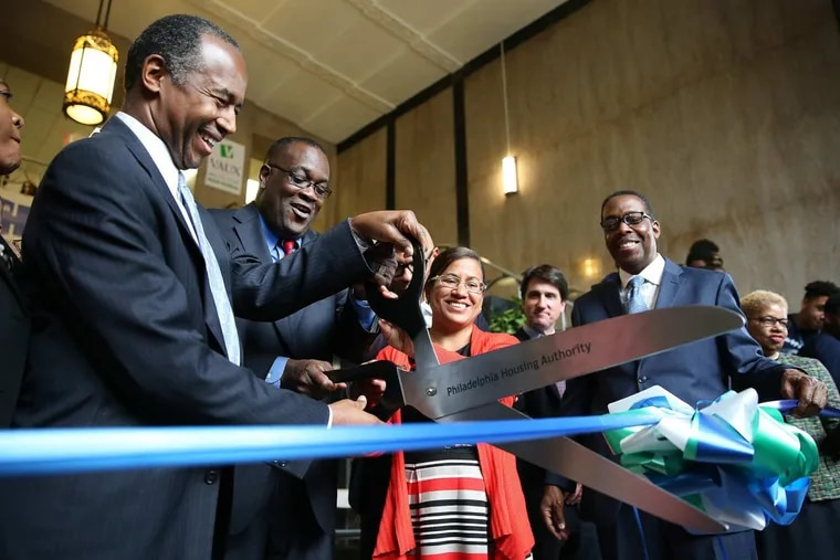 Housing and Urban Development Secretary Ben Carson (left) helps PHA president Kelvin Jeremiah (center) during the ribbon cutting at Vaux Big Picture High School in Philadelphia on Tuesday.