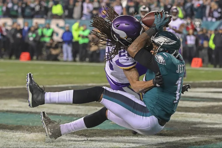 Absorbing a hit from Minnesota's Trae Waynes, Alshon Jeffery scores a fourth-quarter touchdown in the NFC championship game.