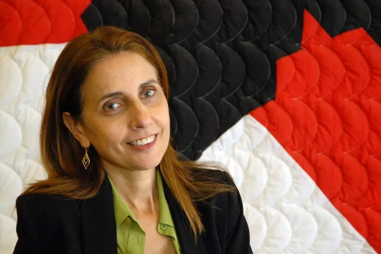 Joyce Ajlouny, the new general secretary of the American Friends Service Committee  (AFSC), sits in front of a quilt that depicts the AFSC symbol, a red and black star.