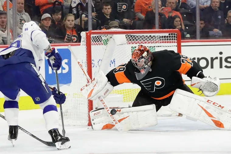 Flyers goaltender Carter Hart, shown stopping a shot taken by Tampa Bay's Nikita Kucherov on Jan. 11, and his teammates will be striving for the Eastern Conference's No. 1 seed when the season resumes.