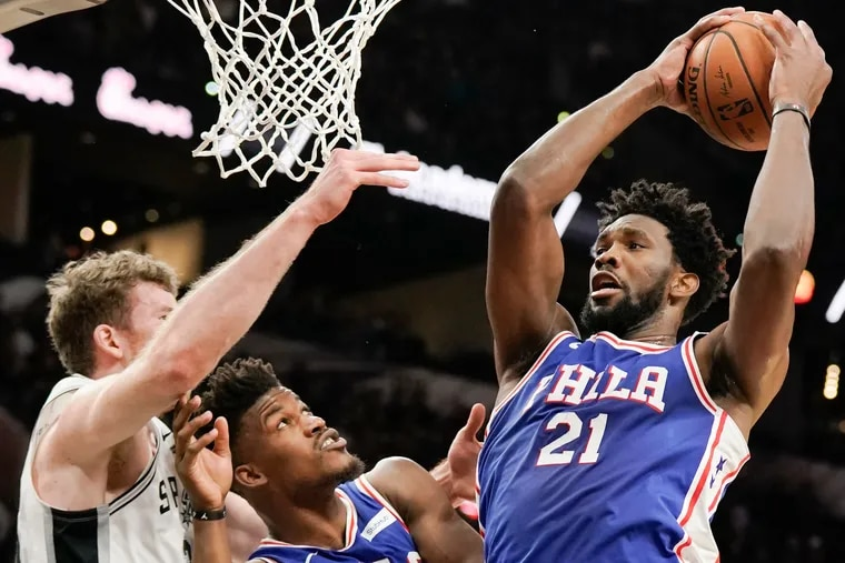 Joel Embiid tries to shoot past the Spurs' Jakob Poeltl (left) and teammate Jimmy Butler during the first half of the Sixers' loss.