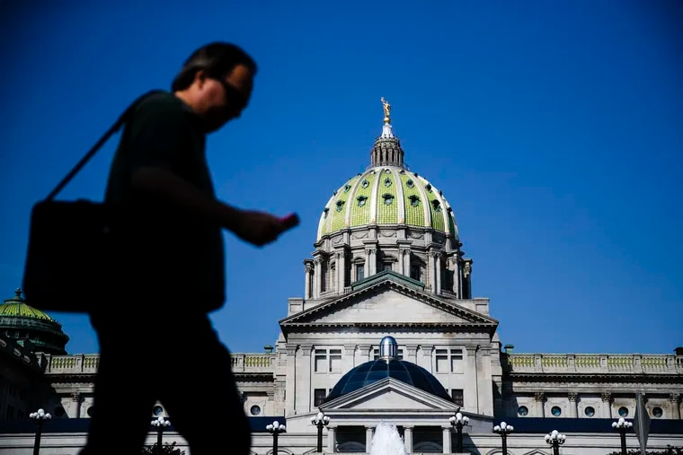 A pedestrian walks by the state Capitol in Harrisburg, Pa. State officials announced plans to close two of its four centers for people with intellectual and developmental disabilities. (AP Photo/Matt Rourke)