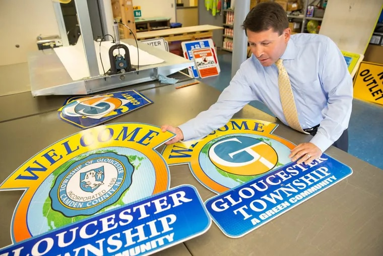 Gloucester Township Mayor David Mayer shown with the old and new township signs.