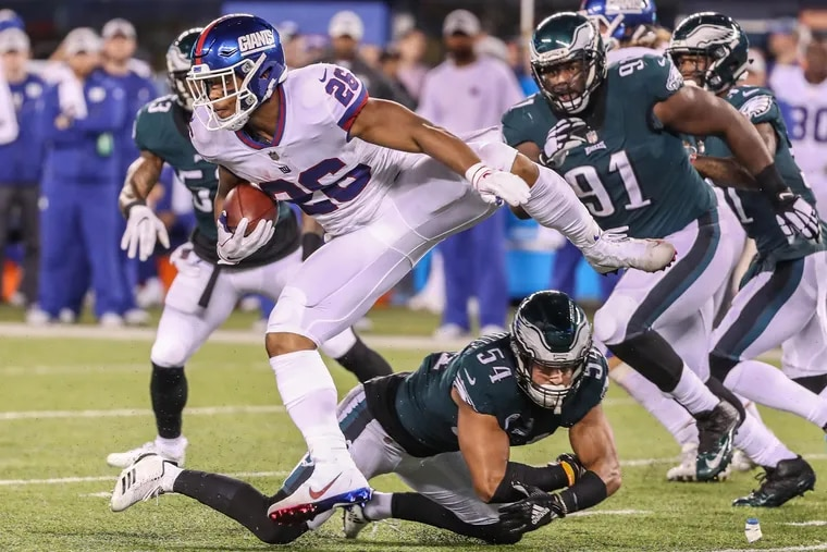 The Giants Saquon Barkley, left, jumps up to avoid the tackle of Eagles Kamu Grugier-Hill, center, for a long gain in the second quarter of Thursdays game. MICHAEL BRYANT / Staff Photographer