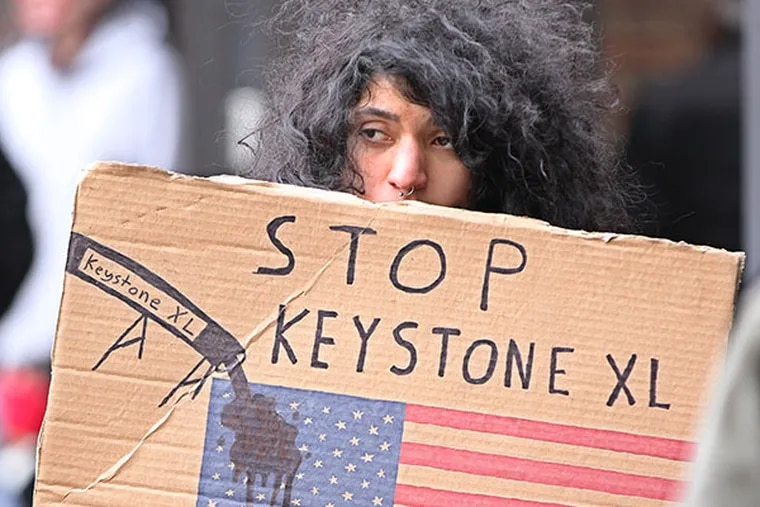 One of the protestors stood in the eastern courtyard of the Federal building protesting the the Keystone XL Pipeline on Monday, March 10, 2014. ( MICHAEL BRYANT / Staff Photographer )