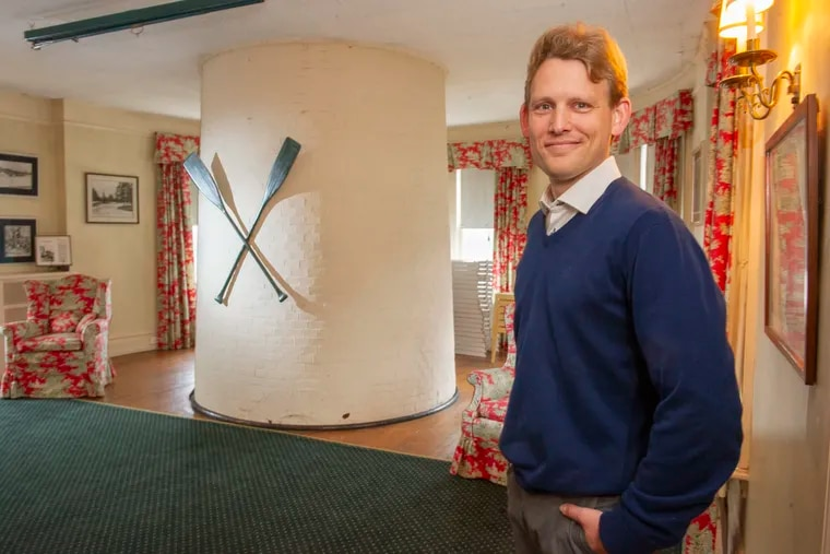 Resident manager Robin Wijngaarden in large living room of the Sedgeley Club on Boathouse Row. Behind him is the base of the club's lighthouse, which extends through the floor into the foundation.