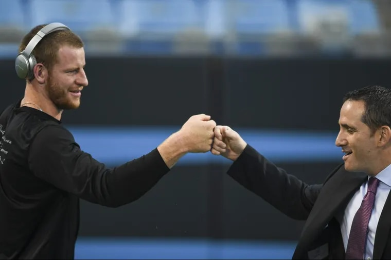 Eagles quarterback Carson Wentz fist bumps with Howie Roseman, Eagles' executive vice president of football operations,before a game against the Carolina Panthers.