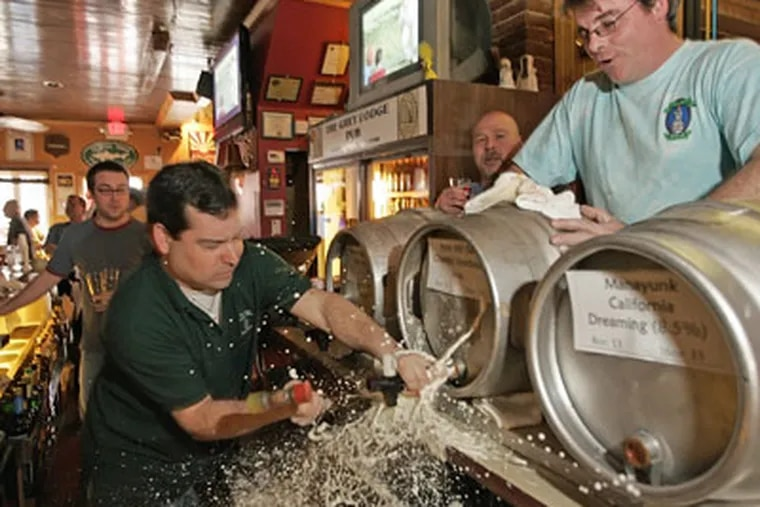 """Mike """"Scoats"""" Scotese tapping a firkin, or small keg, of Iron Hill Bourbon Porter on Friday the 13th last month. Revelers are expected for a similar Beer Week ritual on Friday. (Michael Bryant / Staff Photographer)"""