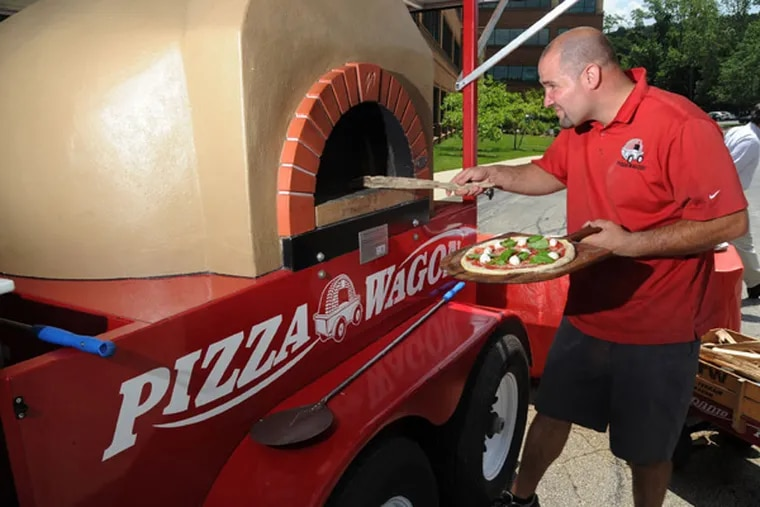 Josh Goldstein, 35, owner of Pizza Wagon lunch truck, slides a pizza into his wood-burning pizza oven outside a King of Prussia office complex June 20, 2013.  Goldstein frequents office complexes, fairs, festivals, little league games and any other venue where people like to eat pizza.  ( CLEM MURRAY / Staff Photographer )