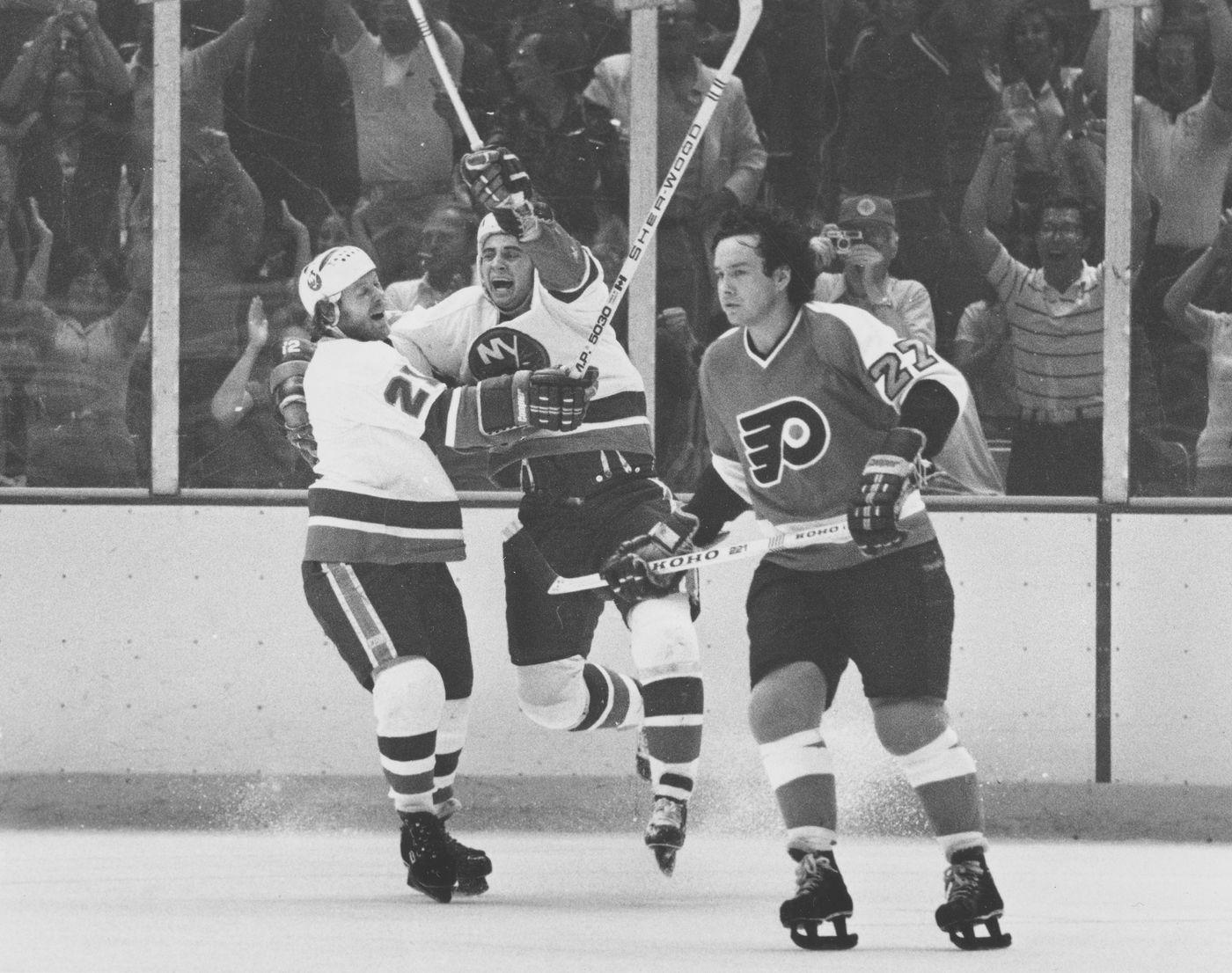 43ba4da47 Reggie Leach skates away as the Islanders  Butch Goring (left) and Duane  Sutter