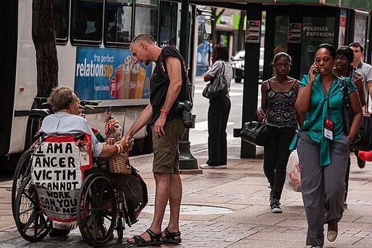 Willie Baronet, a Texas-based artist, speaks with Jim Thomas on Philadelphia's Market Street about the handmade sign Thomas uses to ask for help. July 28, 2014, Philadelphia, Pennsylvania. ( MATTHEW HALL / Staff Photographer )