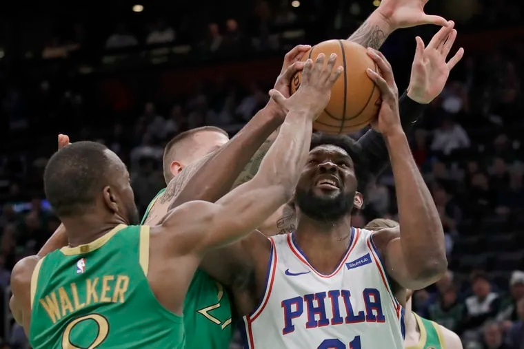 Joel Embiid looks for room to shoot against Boston's  Daniel Theis and Kemba Walker, Embiid finished with 38 points.