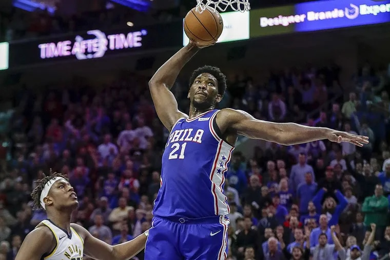 Sixers center Joel Embiid attempts to dunk the basketball against Indiana Pacers center Myles Turner.