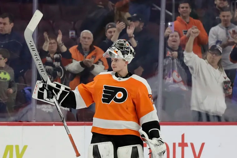 Carter Hart raises his stick after being named the No. 1 star in the Flyers' 2-1 win over the Nashville Predators. Hart made 31 saves in the game.