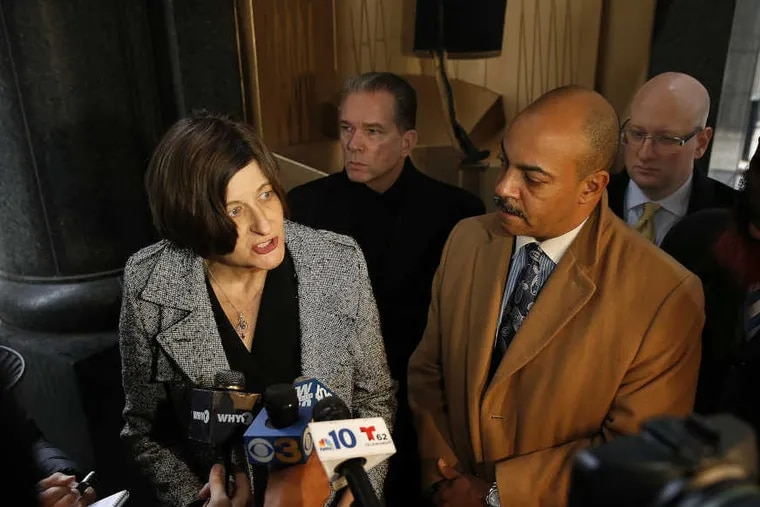 Marissa Boyers Bluestine, legal director of the Pennsylvania Innocence Project, left, stands next to Philadelphia District Attorney Seth Williams outside the Criminal Justice Center in Philadelphia on Dec. 21, 2016, as she speaks about the release of Donte Rollins from prison. Behind them are Mark Gilson (left), director of the District Attorney's Conviction Review Unit,  and Assistant District Attorney Samuel Ritterman.