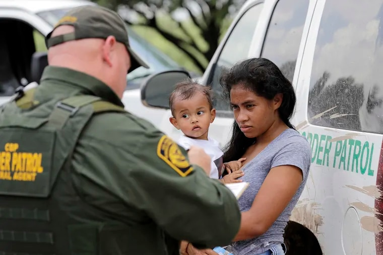 In this June 25, 2018, file photo, a mother migrating from Honduras holds her 1-year-old child as surrendering to U.S. Border Patrol agents after illegally crossing the border near McAllen, Texas. The Trump administration says it would require extraordinary effort to reunite what may be thousands of migrant children who have been separated from their parents and, even if it could, the children would likely be emotionally harmed. (AP Photo/David J. Phillip)
