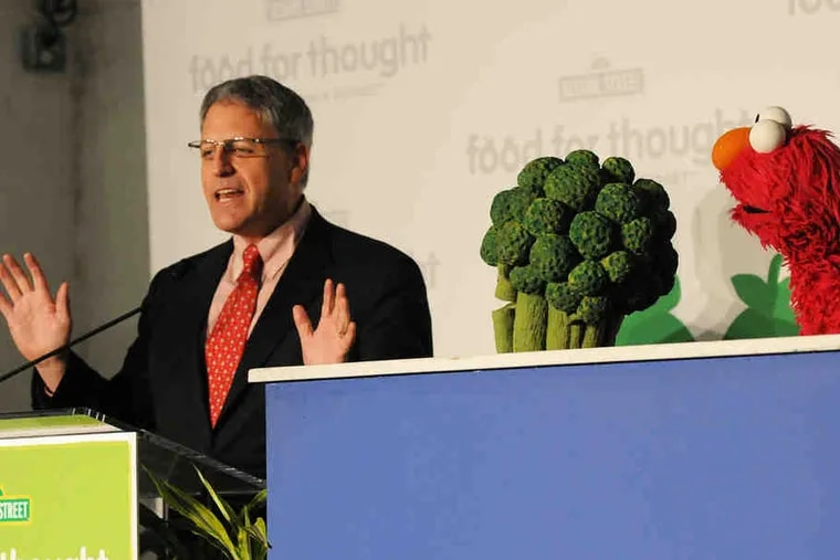 """Sesame Workshop CEO Gary Knell (left), Super Food Broccoli, and Elmo at the event. """"With 'Sesame Street' . . . it changes the whole nature of the conversation,"""" said an advocate."""