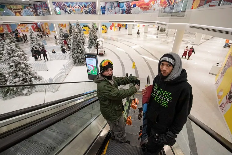 Snowboarders, Brandon Tompkins , left, and Donald Wright, take the escalators to the indoor ski lodge Big Snow inside the American Dream Mall in East Rutherford, N.J.