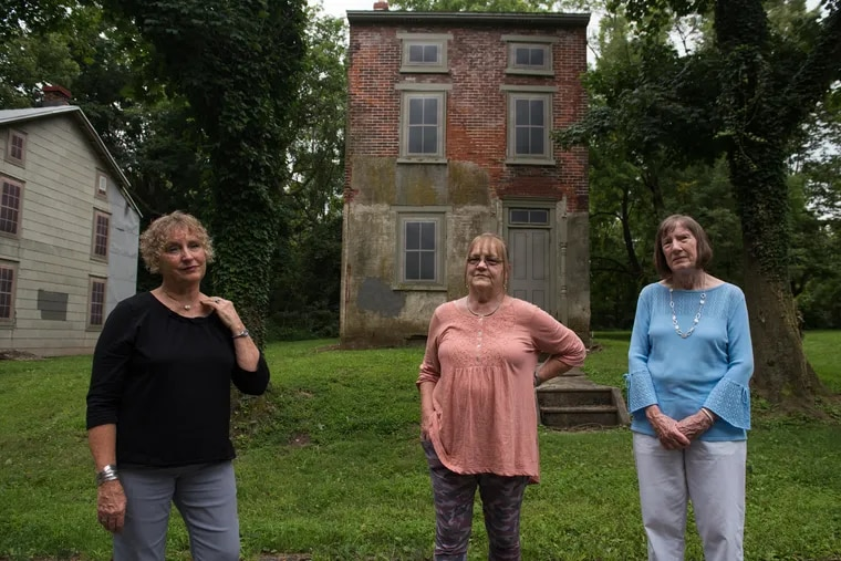 Nancy Fisher, Penny Morton and Donna Mellott, the oldest of ten children, stand in front of their childhood home in the village of Fricks Lock on Tuesday, July 31, 2018. The village was abandoned in the 1970s, following construction of the Limerick Generating Station. Now, the three eldest sisters provide tours of the empty town.