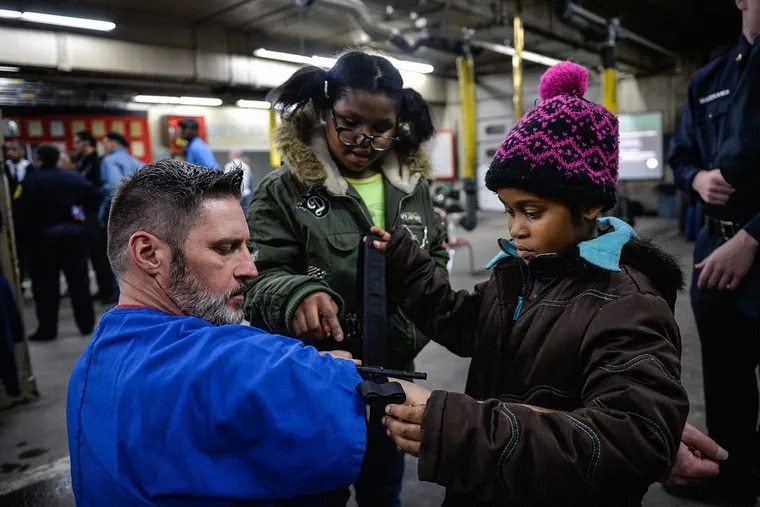 Nurse Edward Bell shows Robyn Ellis, center, and Nasiah Wade, 8, how to apply a tourniquet during a Fighting Chance neighborhood training event.
