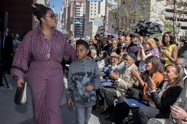 Philadelphia singer Jill Scott, walking with her son Jett Roberts, 8, blows kisses to some of her fans who attended the 2017 Philadelphia Music Alliance Walk of Fame ceremony on the Avenue of the Arts October 4, 2017. Applauding Ms. Scott are (from left) Kathy and Kim Sledge from the group Sister Sledge, and songwriter/record producer Ken Gamble.
