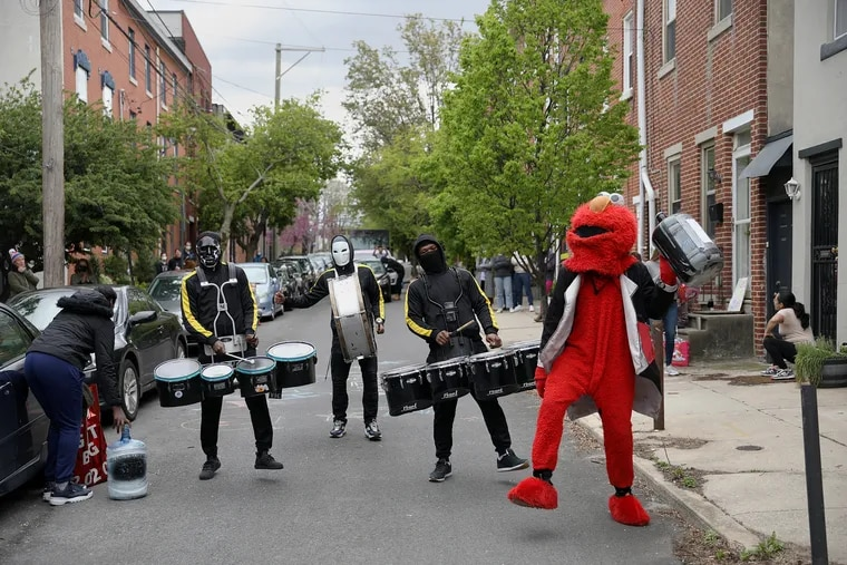 William Fulton, dressed as Elmo, and Positive Movement Entertainment drill team members (from left) Ron Dorman, Donte Thomas, and Tony Royster perform as a birthday surprise for Zori Amaya, 8, outside her home in Philadelphia's Northern Liberties section. The drumline has been the subject of several viral videos.