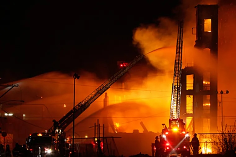 Firefighters battle a five-alarm fire in a warehouse on York Street near Kensington Avenue in the Kensington section of Philadelphia on Monday April 9, 2012.  (Joseph Kaczmarek)
