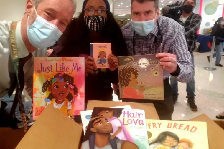 St. Christopher's pediatricians Hans Kersten (left) and Dan Taylor (right) with Harriett's Bookshop owner Jeannine Cook and some of the books in the fundraising Reading Tournament for the Reach Out and Read Program.
