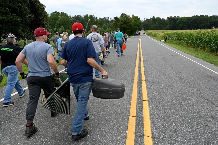 Members and volunteers head out from Fellowship Bible Church Sunday, walking down closed roads to help clean up the property of neighbors following the destruction from a tornado spawned by the remnants of Hurricane Ida.