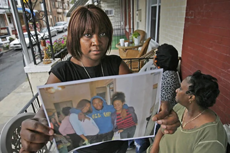 Felicia Travis holds a family photo of her nephew Troy Travis, who was shot and killed yesterday. (Alejandro A. Alvarez / Staff Photographer)