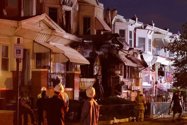 Philadelphia Fire fighters attend to a home on the 5800 block of Chestnut Street in West Philadelphia on Monday, August 2, 2021.  Two people were found dead and two others were injured in a house fire that also damaged four neighboring homes.