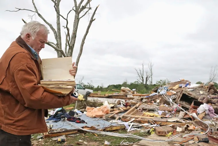 Robert Scott looks through a family Bible that he pulled out of the rubble Sunday from his home outside of Hamilton, Miss., after an apparent tornado touched down Saturday night.