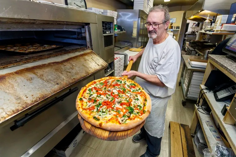 Franco Buscemi, owner of Thin & Crispy Pizza, pulls a Vegetarian Delight large pizza out of the oven at his pizzeria on Trenton Avenue.